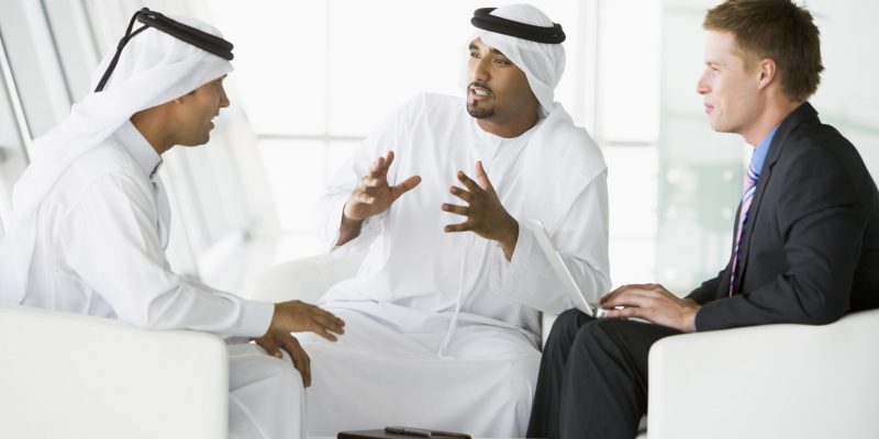 A meeting between a Caucasian businessman and two Middle Eastern